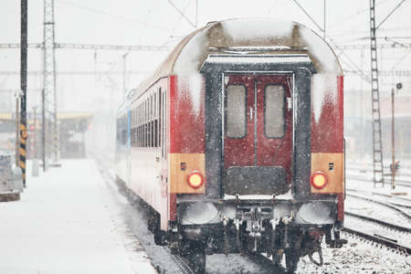 Travel in winter. Train is coming to the railroad station during heavy snowfall.
