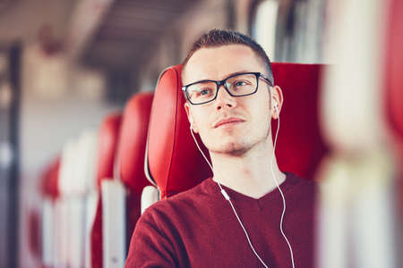 Rail transportation. Thoughtful young man with eyeglasses listening to music while traveling by train. Stock Photo