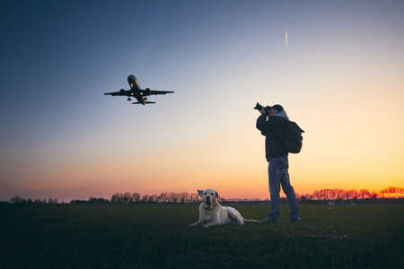 Young man with dog is photographing near airport. Airplane landing aginst moody sky sky at golden sunset.