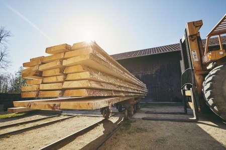 Industria maderera. Tablones de carga del cargador de ruedas en el aserradero al amanecer. Foto de archivo
