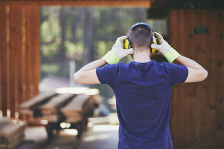 Man working in sawmill. Rear view of the worker with headset.  Stock Photo