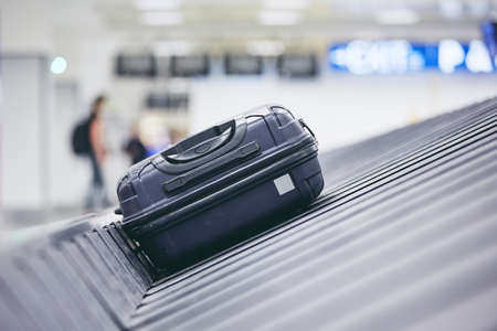 Traveling by airplane. Suitcase on baggage claim in airport terminal. 写真素材