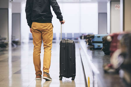 Man traveling by airplane. Young passenger holding his suitcase near baggage claim in airport terminal. Banque d'images - 101258291
