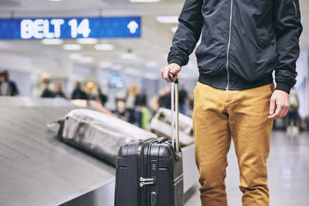 Man traveling by airplane. Young passenger holding his suitcase near baggage claim in airport terminal.