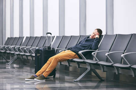 Man traveling by airplane. Tired passenger sleeping in airport terminal.