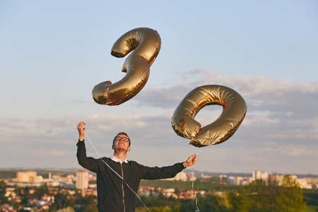 Man celebrates thirty years birthday. Person holding helium balloons in shape of number 30 against city.