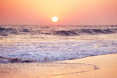 Idyllic sunset on the empty tropical beach. Selective focus on foam on the sand against moody sky.