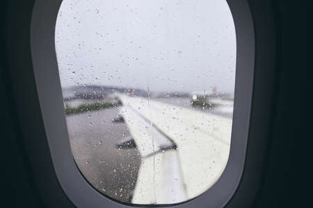 Close-up of airplane window during rain. Selective focus on raindrops.