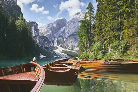 Wooden boats on lake. Beautiful sunny morning at Lago di Braies in Dolomite Alps - South Tyrol, Italy