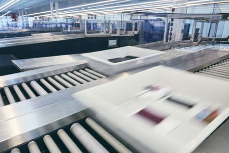 Airport security check. Containers with personal belongings (in blurred motion) on conveyor belt after x-ray control.