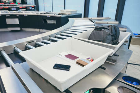Airport security check. Containers with personal belongings (passport, smart phone, wallet, keys) before x-ray control.