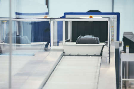 Airport security check. Containers with luggage on conveyor belt after x-ray control.