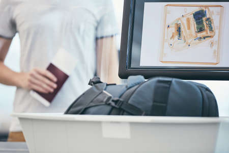 Airport security check. Young man holding passport and waiting for x-ray control his luggage. Stock Photo