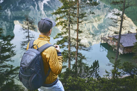 Young man (tourist) with backpack is walking throught forest. Mountains refelection in Lake Braies, Italy.