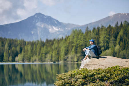 Young man (tourist) resting on rock above lake against mountain range of Alps. Pure nature in South Tyrol in Italy. Stock Photo