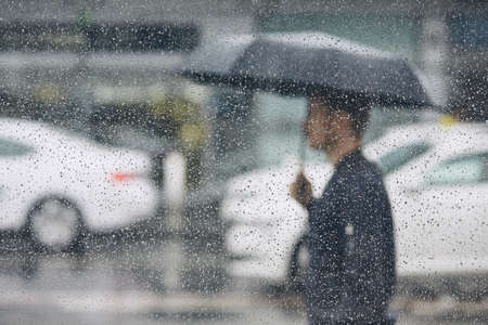 Rain in city. Young man holding umbrella walking in the street. Selective focus on  raindrops on the window. Imagens - 103355440