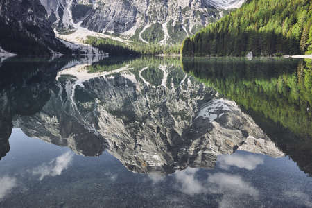 Reflection of the mountain in the water. Amazing view of Braies Lake (Lago di Baraies) in Alps, Italy.
