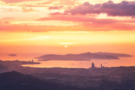 View of silhouette landscape with Kota Kinabalu city against islands at golden sunset.  Sabah state, Malaysia.