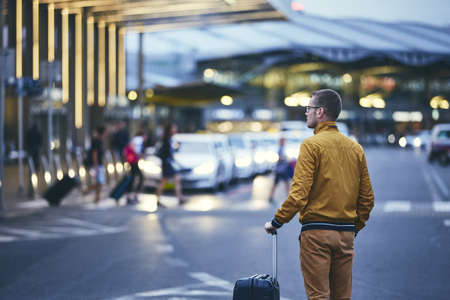 Passenger walking outside airport terminal. Rear view of young man with luggage at night. Stok Fotoğraf