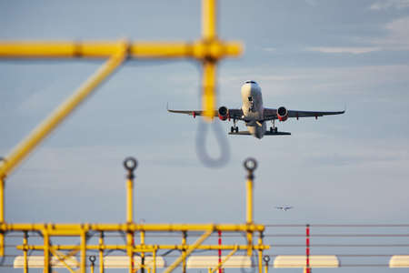 Traffic at the airport. Low angle view of the airplane during take off over landing lights. Stock Photo