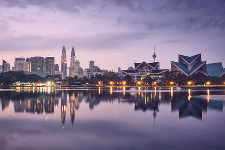 Moody sunrise in Kuala Lumpur in Malaysia. Reflection of the urban skyline in the lake. Redactioneel