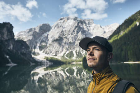 Young man (tourist) in nature. Mountains refelection in Lake Braies, Italy.