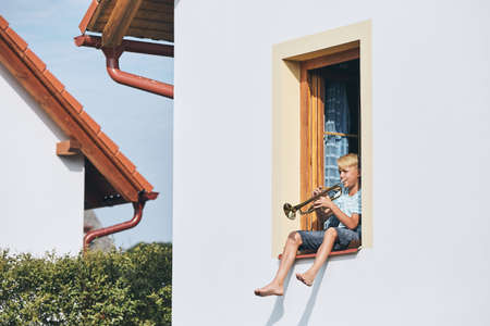 Little boy playing the trumpet in open window of the house. Stock Photo