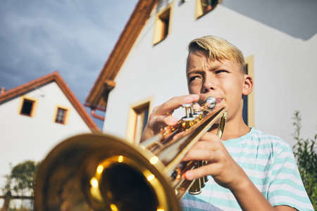 Little boy playing the trumpet in front of the house. Stock Photo