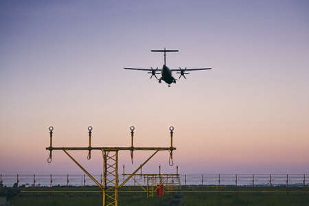Airplane landing at dusk. Turboprop aircraft approaching to airport.