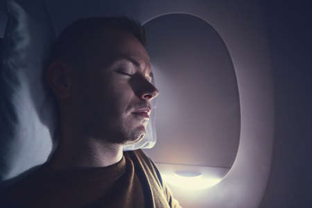 Traveling by airplane. A passenger sleeping during flight.