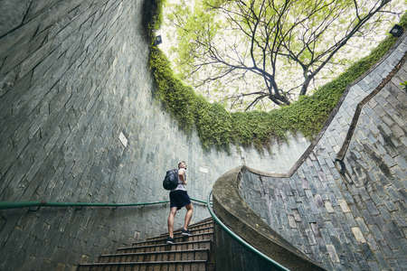 Young man (tourist) walking up on the spiral staircase of underground walkway in Singapore.
