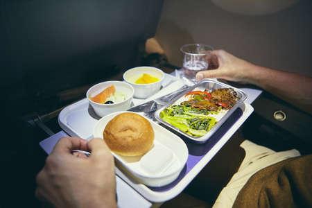 Viajando en avión. Pasajero disfrutando de una cena en clase económica durante un vuelo de largo recorrido. Foto de archivo