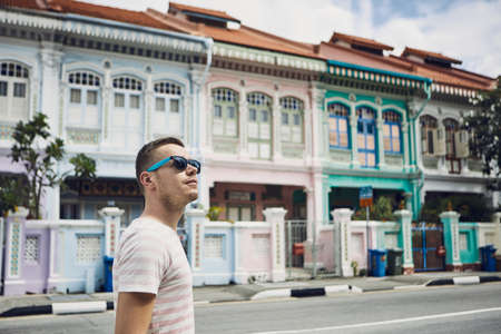 Tourist with sunglasses walking throught old street in Singapore. Colorful houses with combined Malay, Chinese, Indian and western architecture and culture.
