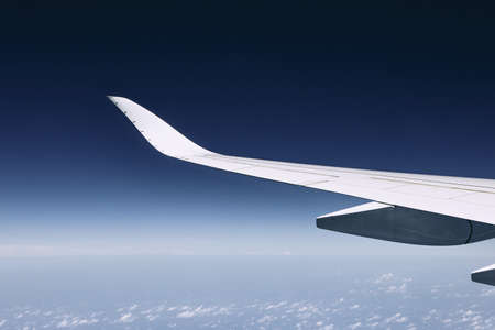 Wing of modern airplane flying over clouds against dark blue sky. Stok Fotoğraf
