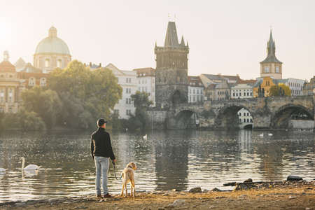 Morning walk with dog. Young man and his labrador retriever on riverbank against Old Town with Charles Bridge in Prague.
