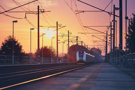 Passenger train commuting to railroad station at colorful sunrise. Stok Fotoğraf - 109961691