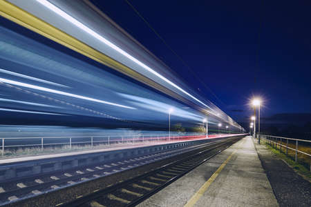 Light trails of passenger train commuting to railroad station at night.