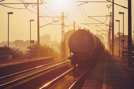 Freight train leaving from railroad station at sunrise.