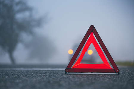 Traffic problem in thick fog. Car on the road behind warning triangle. Imagens - 111479370