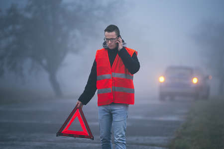 Traffic problem in thick fog. Young driver calling for assistance and putting warning triangle behind his broken car.