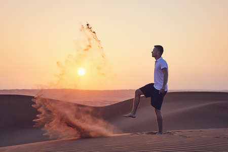 Happy man kicking sand and having fun in desert at sunrise. Wahiba Sands in Oman