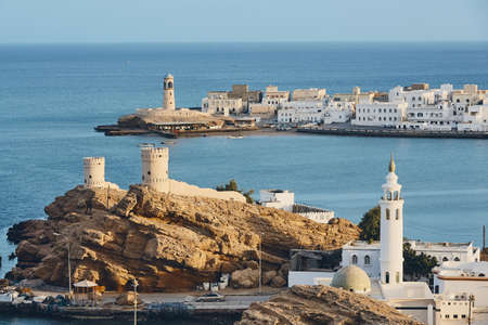 Lighthouse, watchtowers and white houses of traditional architecture of old town Sur in Sultanate of Oman.