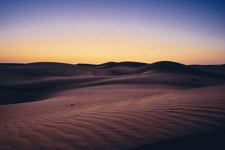 Sand dunes against sky before sunrise. Desert Wahiba Sands in Oman.