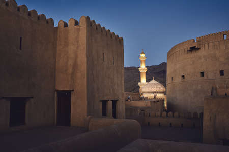 Evening view between watchtowers of historic fort to illuminated mosque. Nizwa, Sultanate of Oman.