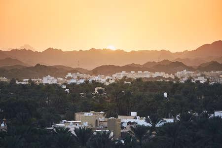 City against mountain range at idyllic sunset. Nizwa in Sultanate of Oman.