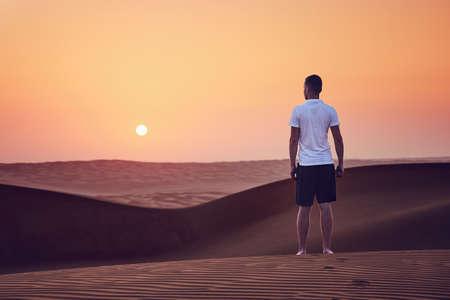Sunrise in desert. Lonely man walking on sand dune. Wahiba Sands in Oman.