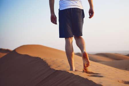 Jeune homme marchant au sommet d'une dune de sable. Wahiba Sands à Oman.