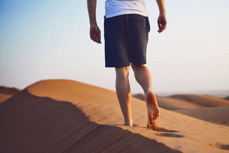 Young man walking on top of sand dune. Wahiba Sands in Oman.
