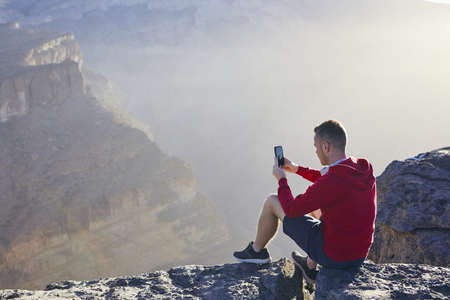 Relaxation in mountains. Young man photographing by mobile phone. Jebel Akhdar, Grand Canyon of Oman.