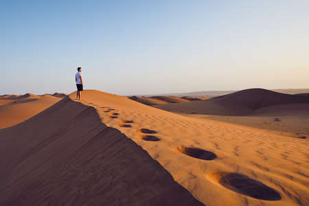 Young man standing on top of sand dune and looking at view. Desert Wahiba Sands in Oman. 免版税图像
